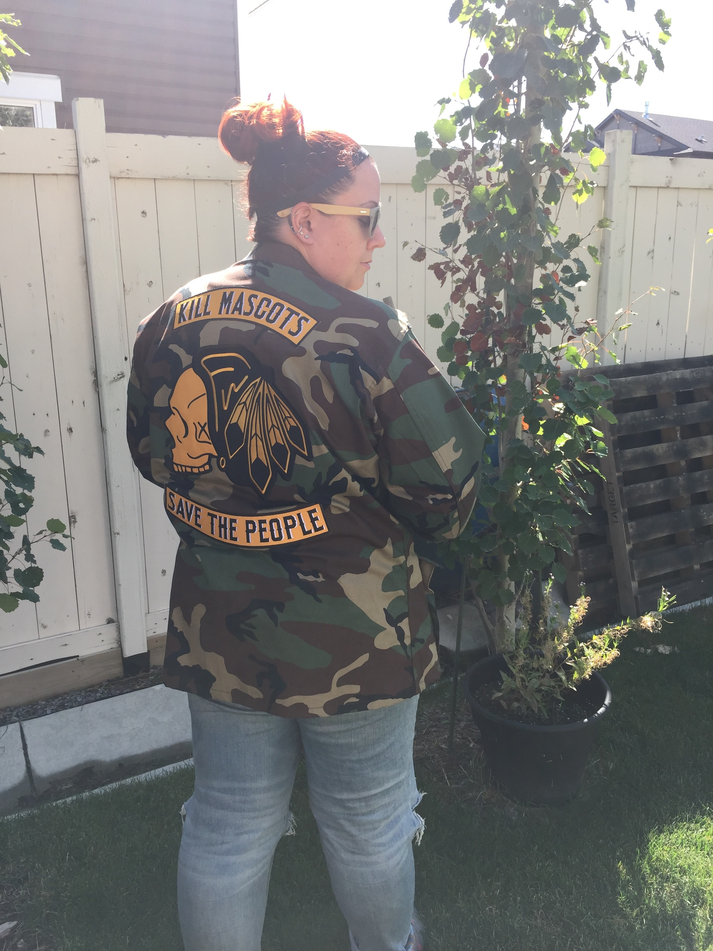 """91fa920d744 It is a camouflage jacket with a re-crafted giant Chicago Blackhawks skull  logo on the back saying """"Kill the Mascots, Save the People""""."""